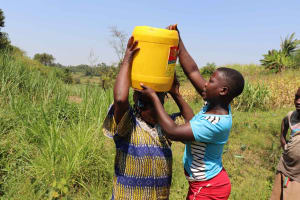 The Water Project: Emulele Community, Fanice Opati Spring -  Helping Elder With Jerrycan
