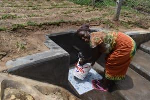 The Water Project: Mukangu Community, Mukasia Spring -  Filling A Bucket