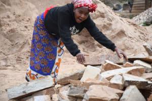 The Water Project: Kyamwalye Community -  Carrying Heavy Rocks