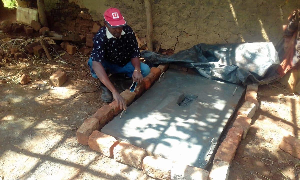 12 kenya4724 Mr. Benard poses at his new sanitation platform