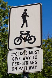 Cyclists give way to pedestrian sign