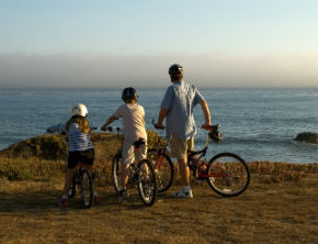 Dad and kids out on a cycling day by the sea
