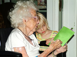 An elderly lady reading to a child