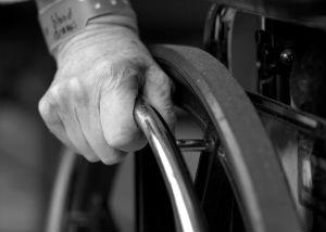 An elderly hand on a wheelchair