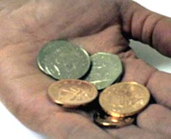 Someone's hand holding loose change - manners cost nothing
