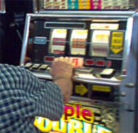 A man playing a slot machine in a gaming area.