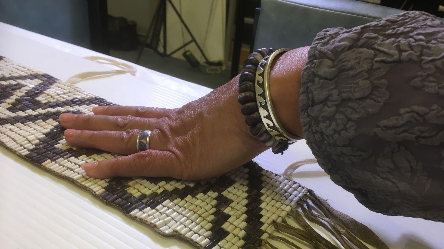 A pair of hands holding a wampum belt