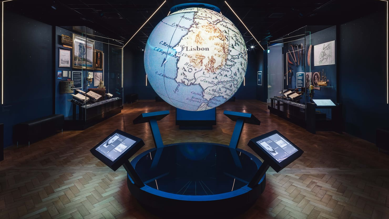 An interactive globe showing a map of the world in a museum gallery (the 100 Journeys gallery at The Box in Plymouth)
