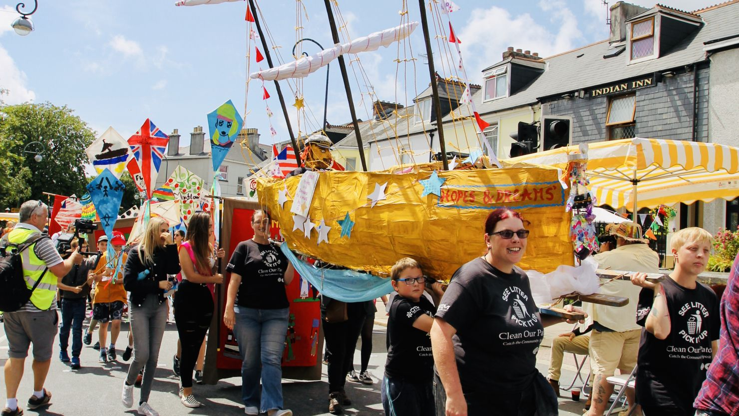 A group of people taking part in a community parade and carrying a boat made from card