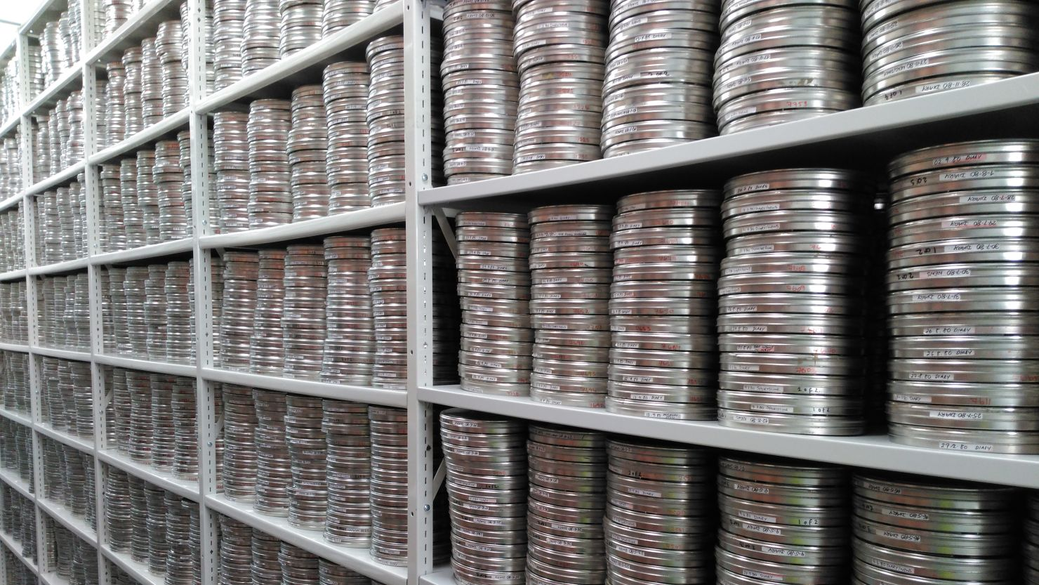 Film reels in silver cases on shelves in an archive store