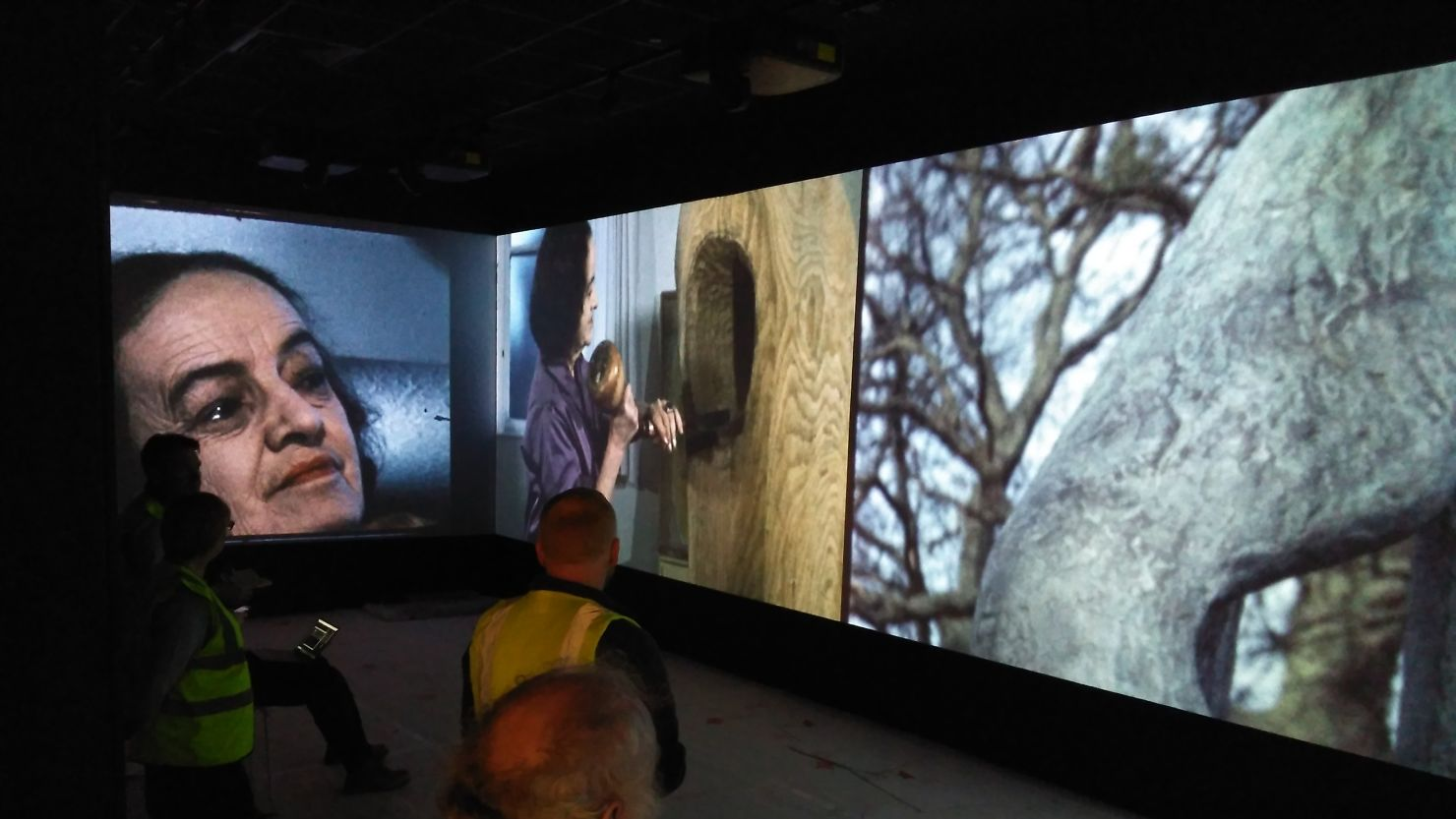 People standing in front of a large screen projection