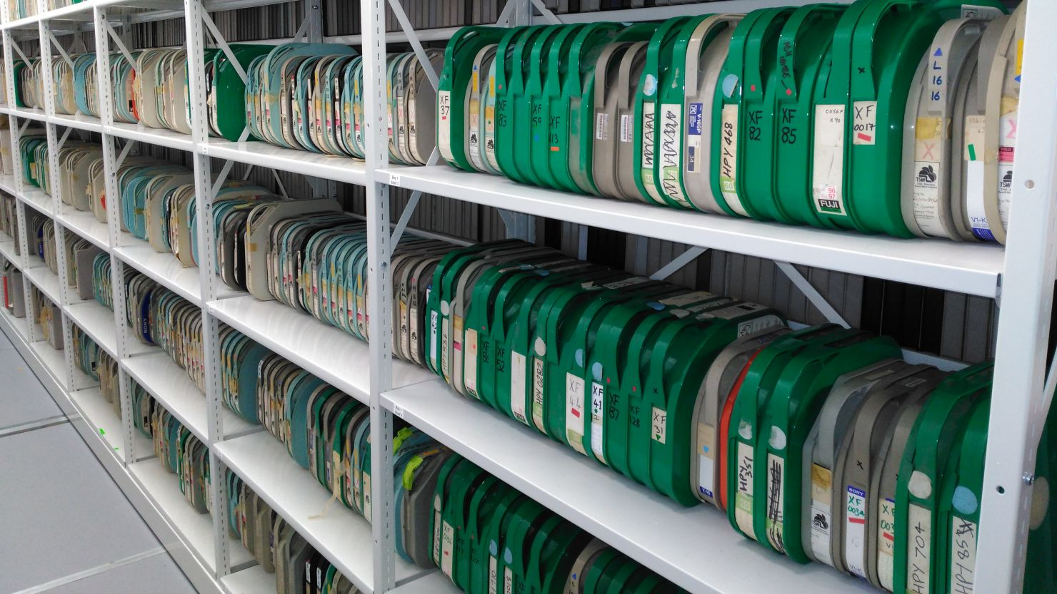 Media tapes in green cases on shelves in an archive store