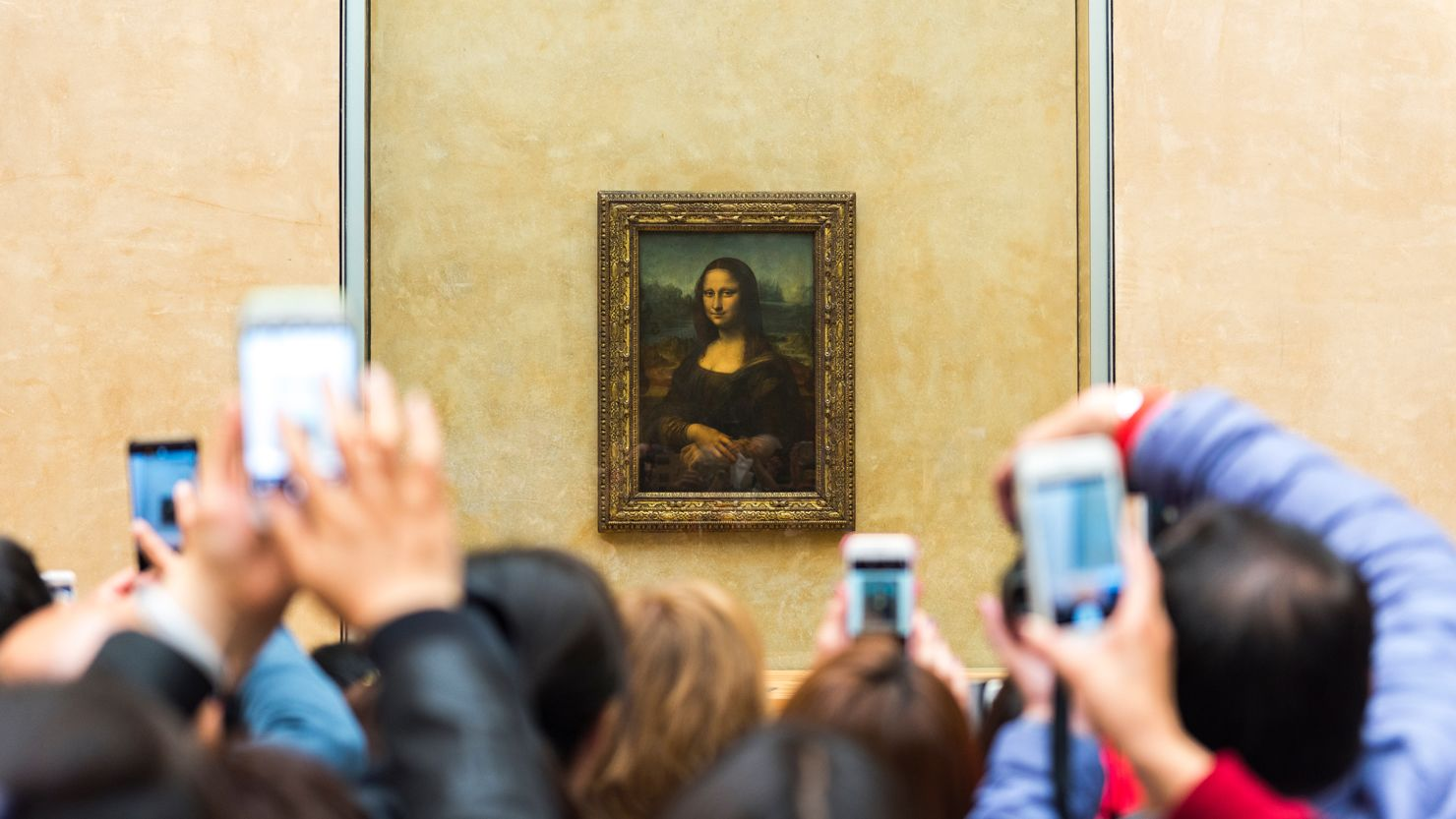 The Mona Lisa being photographed by visitors at the Louvre in 2017