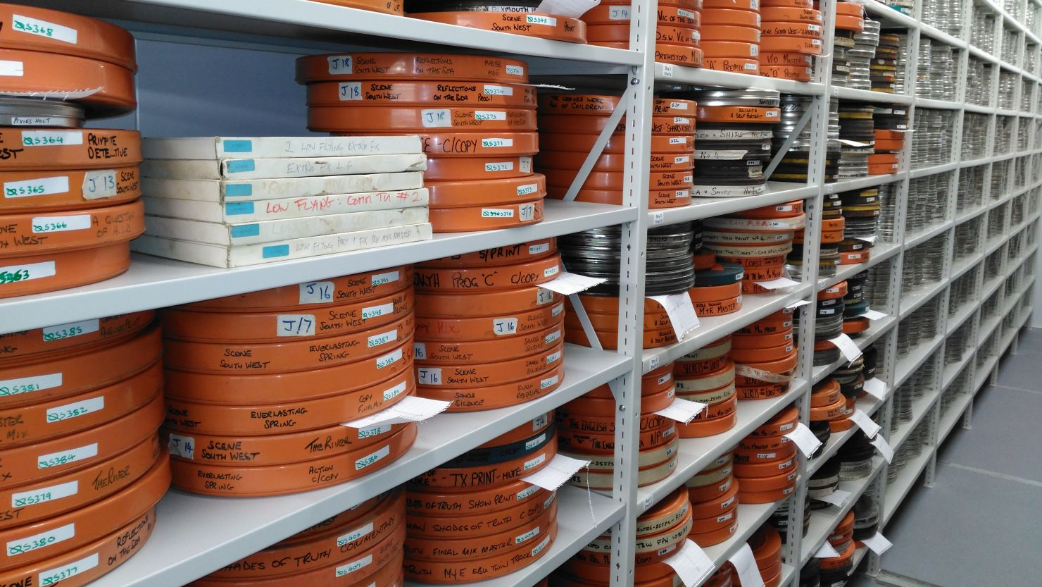 Orange film reels on a shelf in an archive store