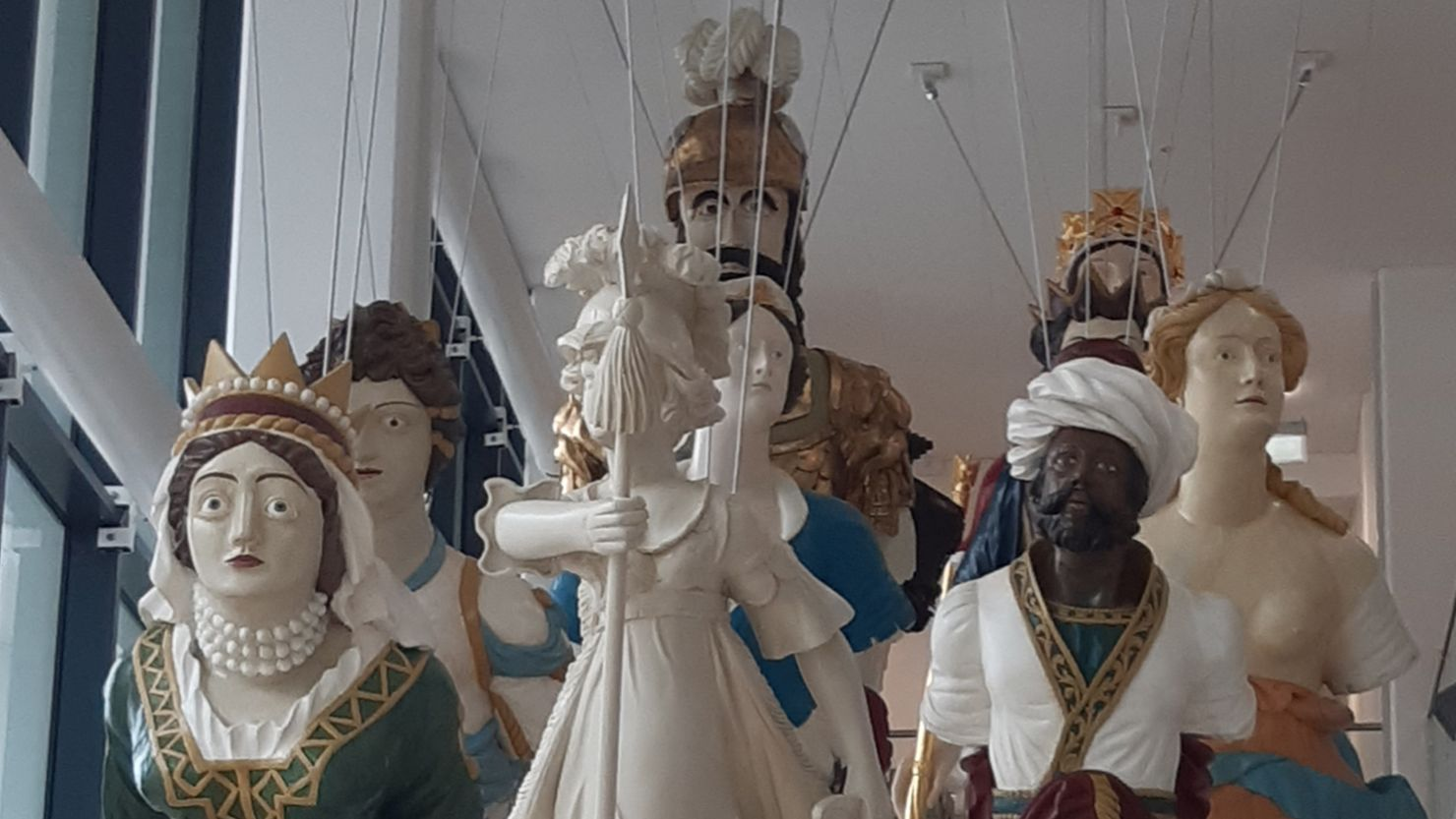Group of historic ship's figureheads suspended from a ceiling