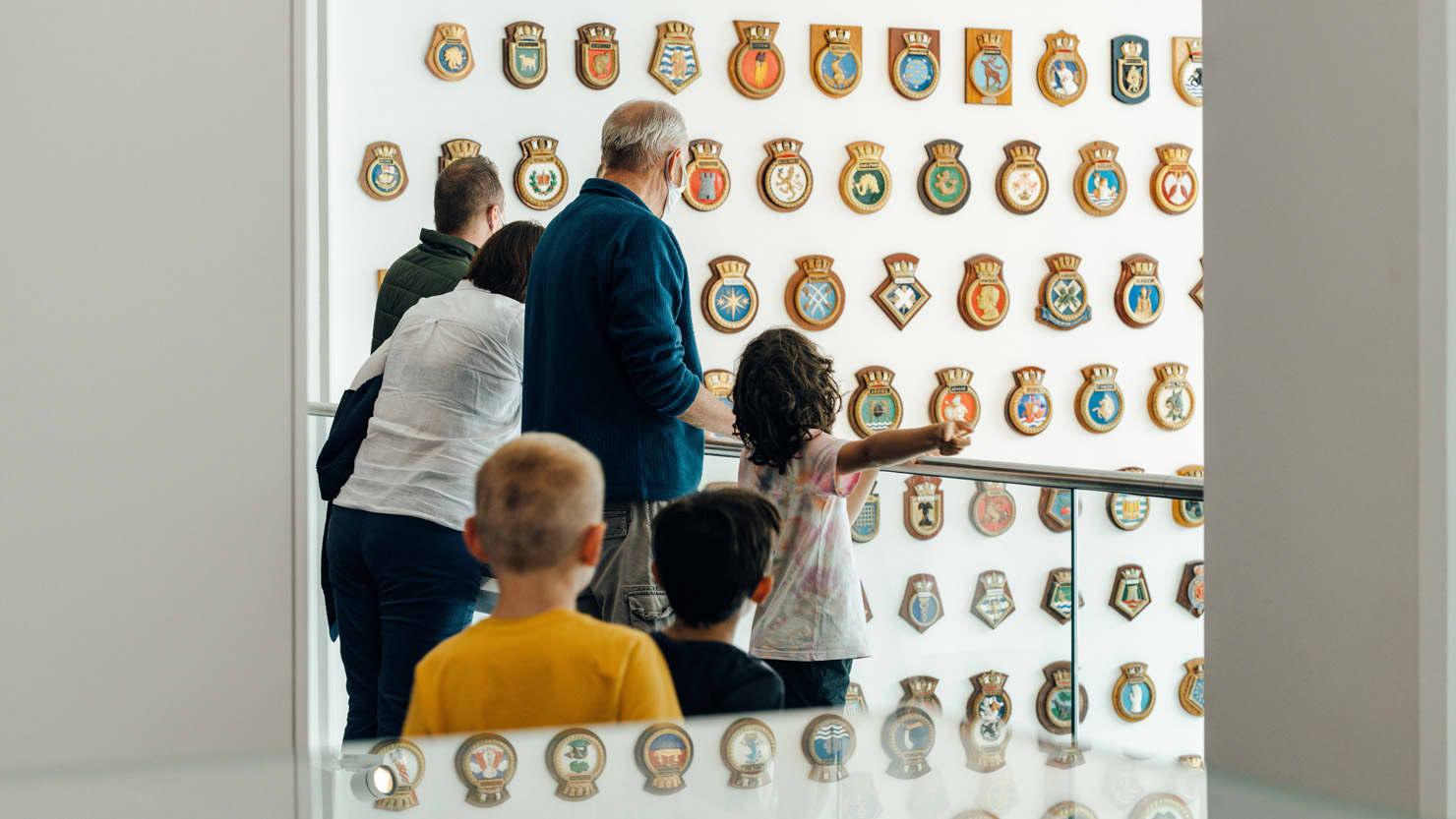 A family looking at the ship's badges at The Box, Plymouth