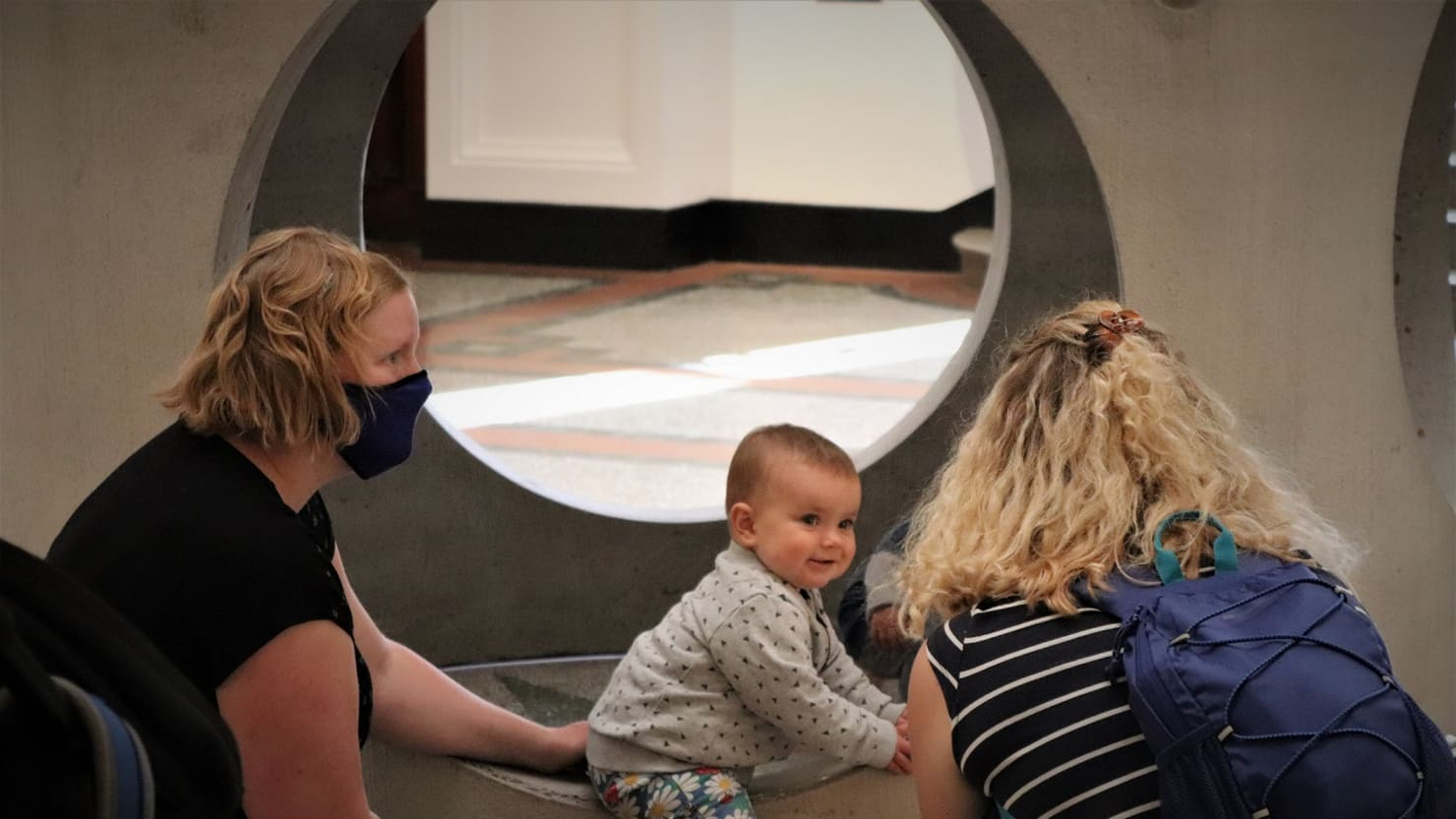 A family with a small baby interact with The Box's 'Figurehead II' sculpture by Alexandre da Cunha