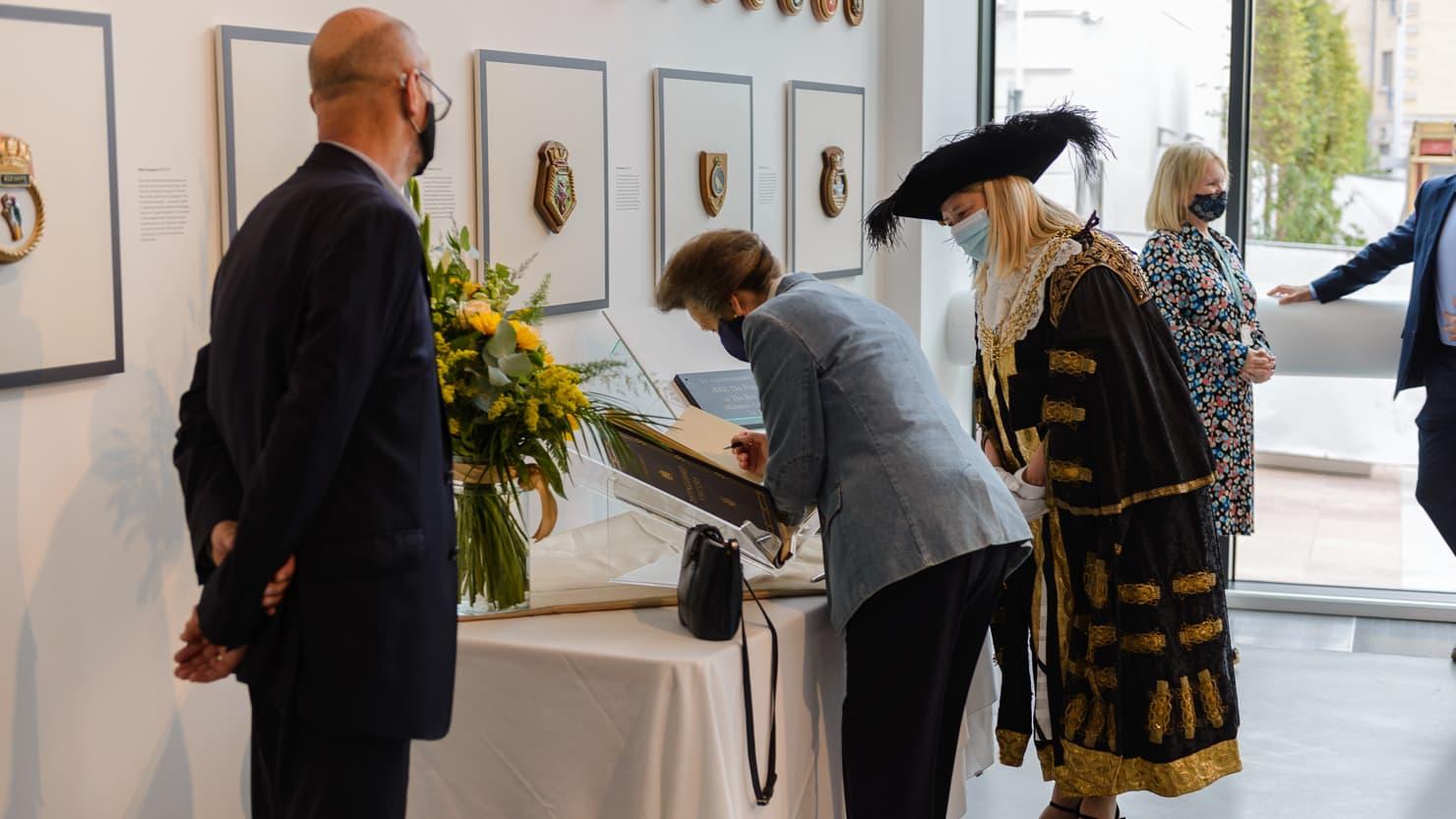 HRH The Princess Royal signing a book at The Box
