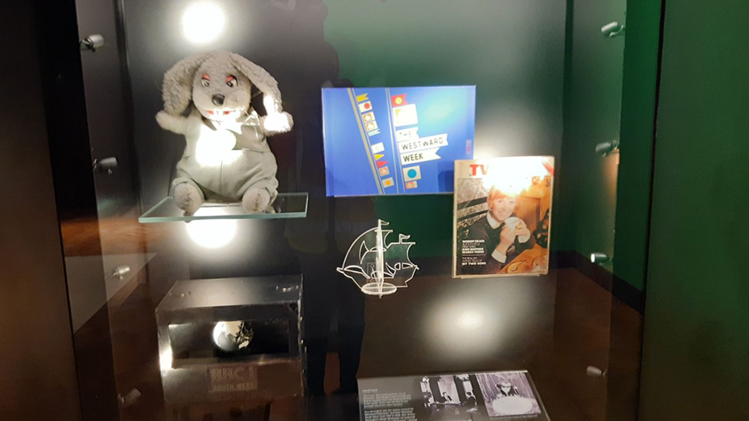 A display of objects in a case including Gus Honeybun