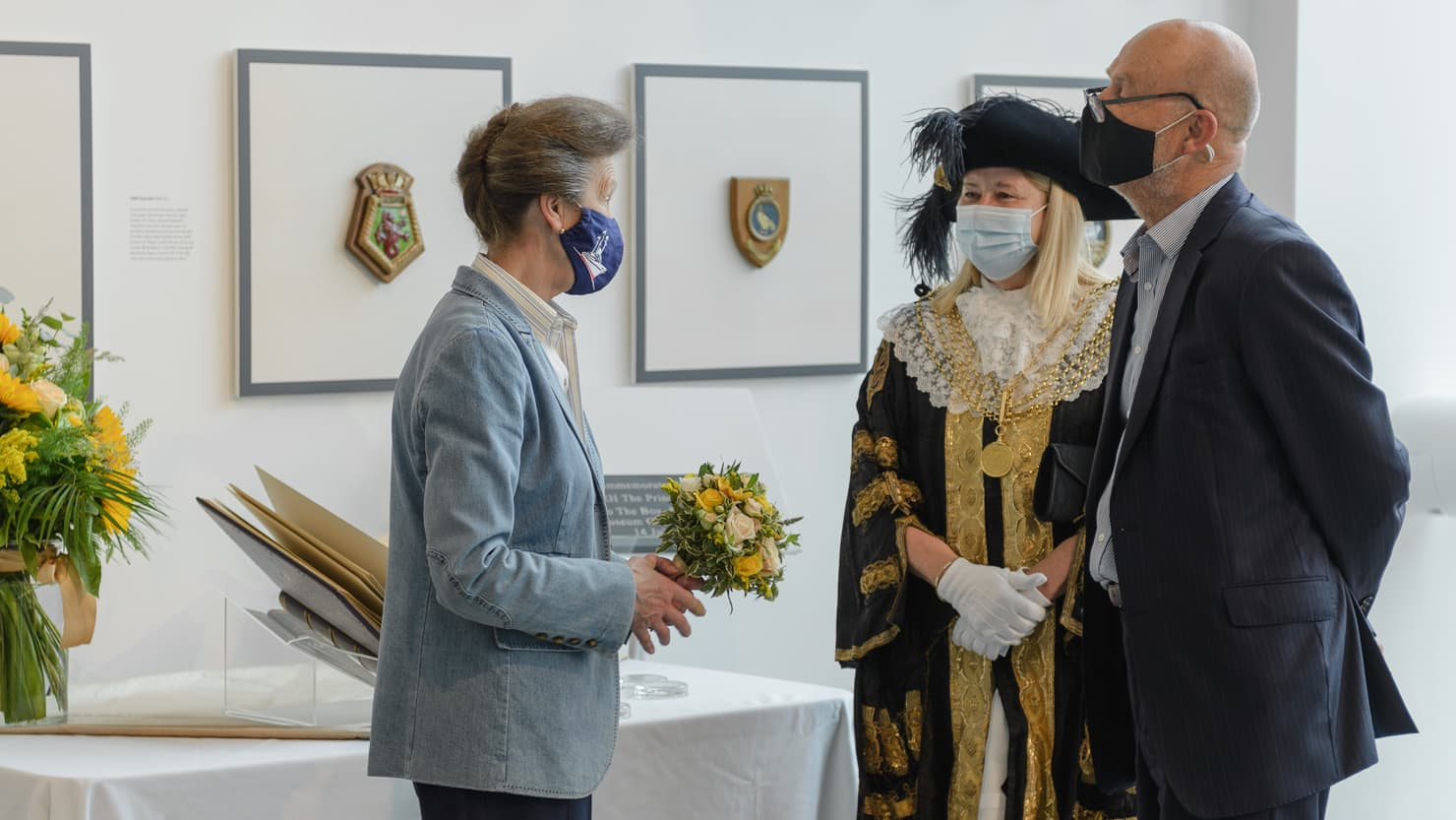 HRH Princess Anne talking to a man and a woman while holding a bunch of flowers