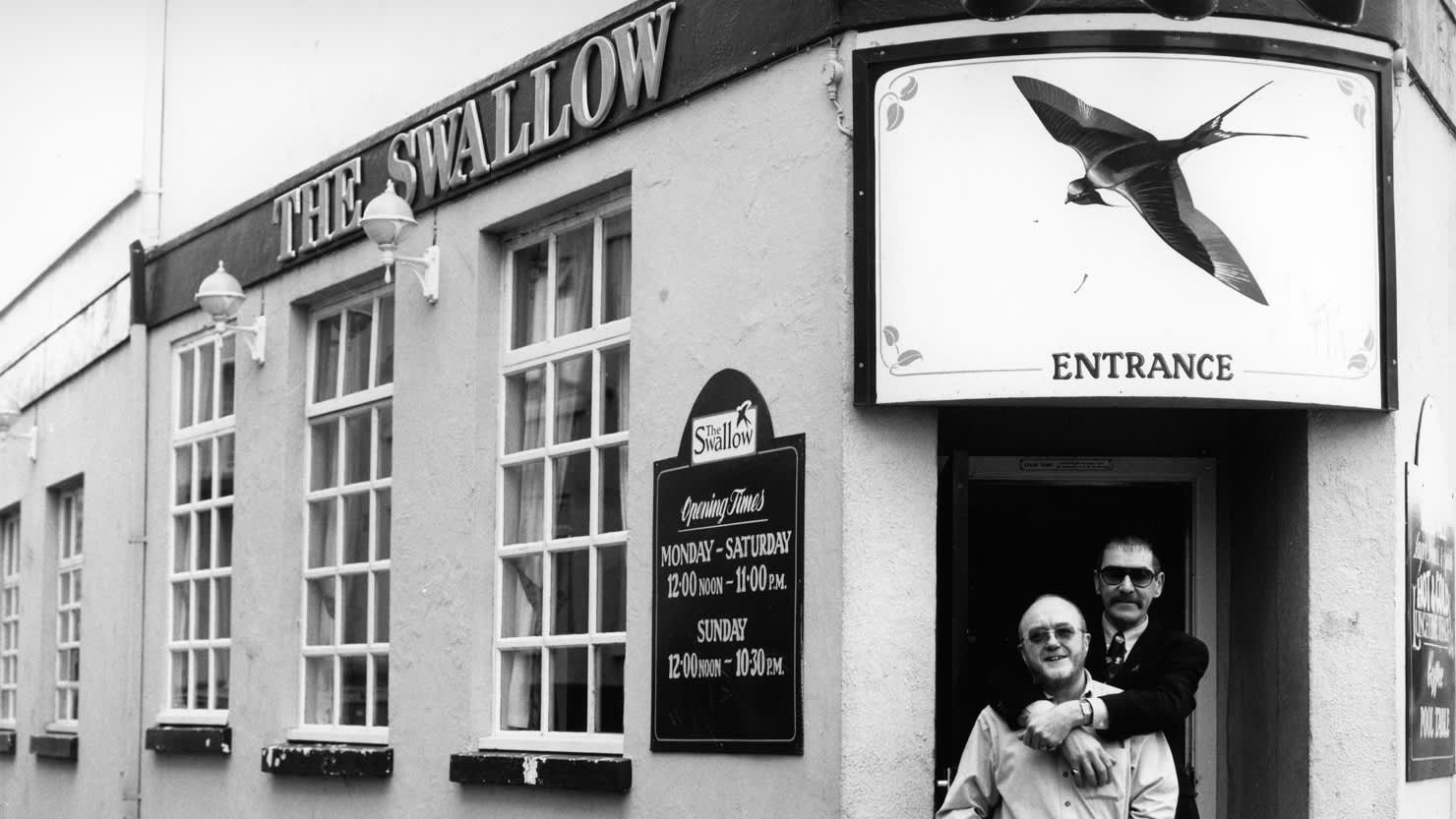 Black and white image of two men standing together in the entrance of The Swallow pub in Plymouth