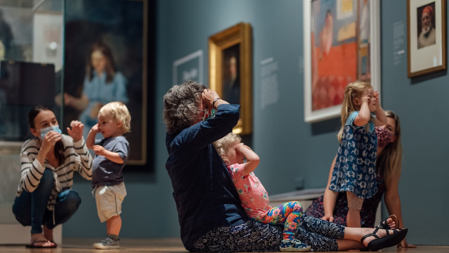 Families making binoculars with their hands to look at paintings