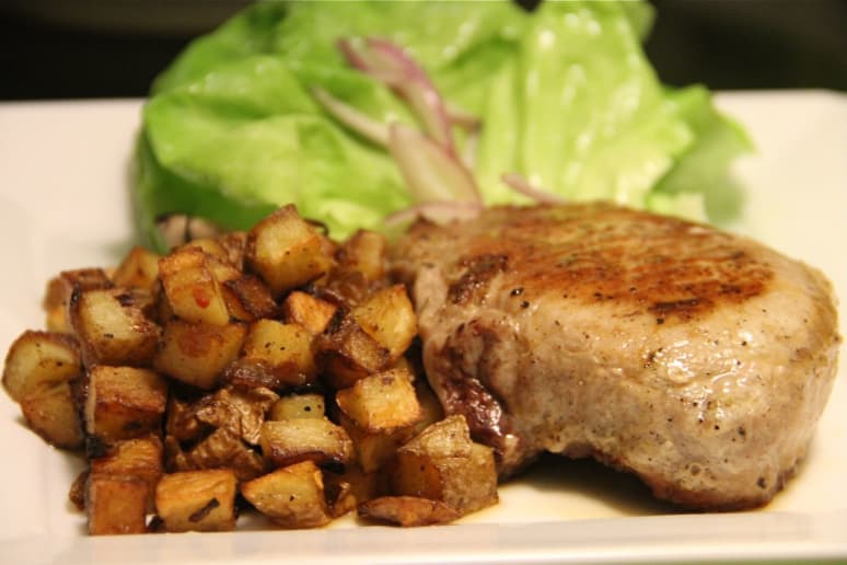 Pork chop with red pepper flake flecked potatoes.