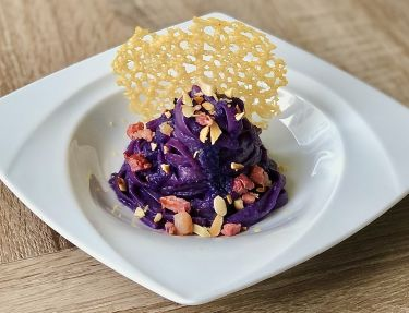 Linguine con crema di cavolo cappuccio viola, pancetta croccante, mandorle e nocciole e cialda di Parmigiano