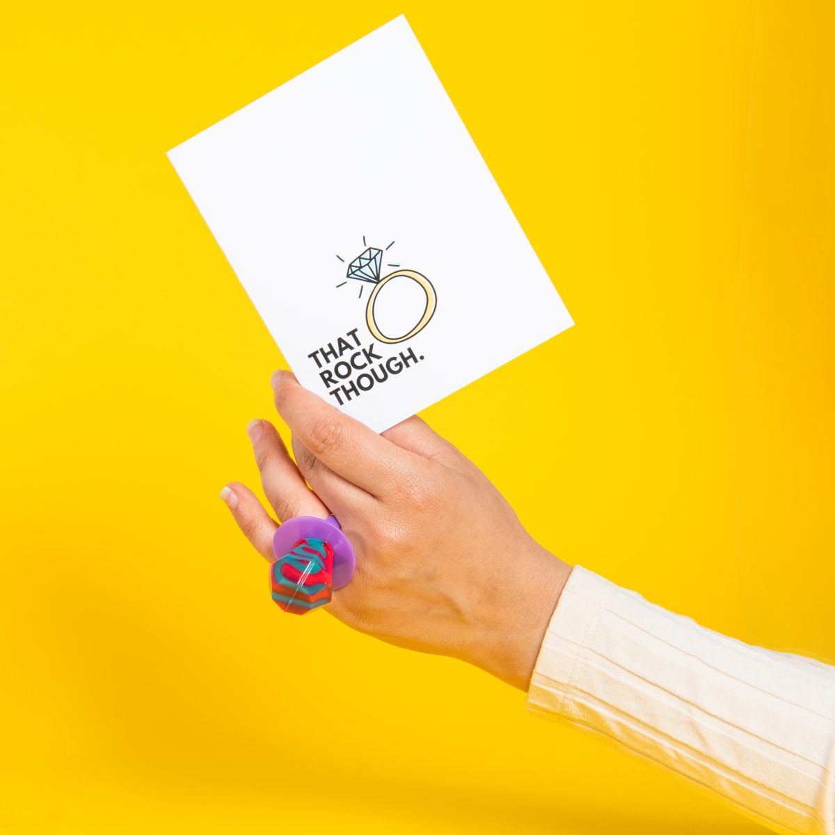 Woman wearing a ring pop holding a card that says 'That rock though'.