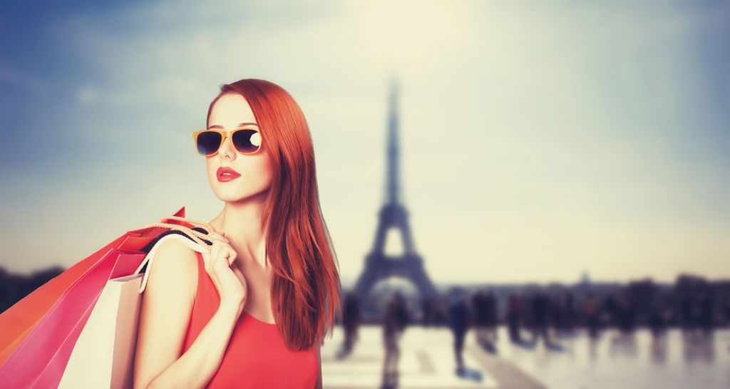 Woman standing in front of the eifel tower with shopping bags