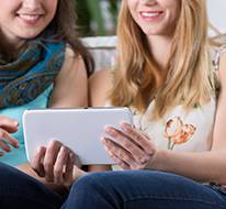 Two women holding a tablet and looking at cosmetic surgery before and after images.