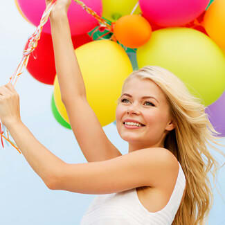 Woman holding a bunch of colourful balloons against a blue skin.