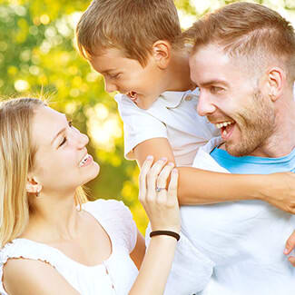 Blonde mother looking up at son on father's back while they're all smiling in the park.