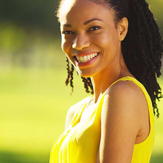 Woman smiling over her shoulder and wearing yellow dress at the park.