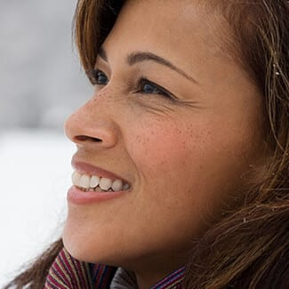 Woman's profile as she smiles and looks slightly up showing youthful eye contour.
