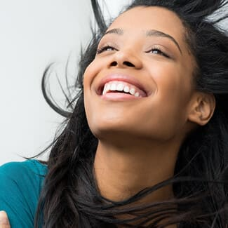 Young woman tossing head back and smiling and wearing a blue shirt.