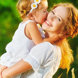 Mother holding daughter who is kissing her on the cheek who are both wearing white dresses in the park.