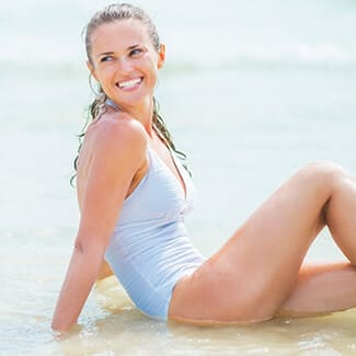 Woman wearing bathing suit looking over her shoulder and smiling as she sits in the water at the beach.