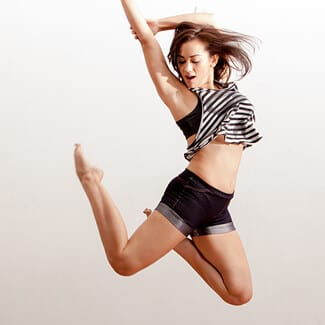 Young woman wearing a striped shirt and shorts jumping up in mid air while dancing.