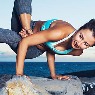 Woman in blue top and pants performing complex yoga pose on rock at the beach.
