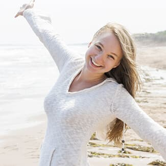 Woman wearing white shirt at the beach with hands outstretched and smiling.