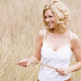 Woman wearing white dress and holding a stalk of straw and smiling.