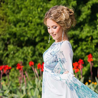Woman wearing blue dress with hair upswept in bun as she walks through a garden with pretty flowers.