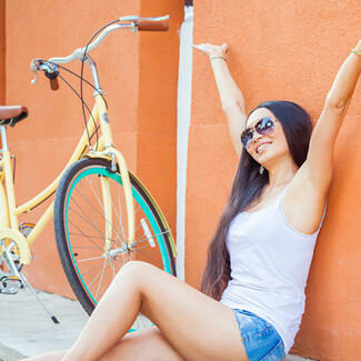 Woman wearing tank top and shorts as she sits on the ground with her hands stretched upwards beside a bike with her back against an orange wall.