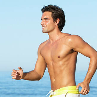 A man wearing swimming trunks running on the beach.