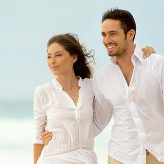 A man and woman wearing white clothes and hands around each other as they walk on the beach.