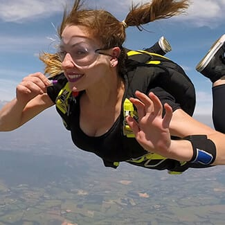 Woman skydiving and smiling.
