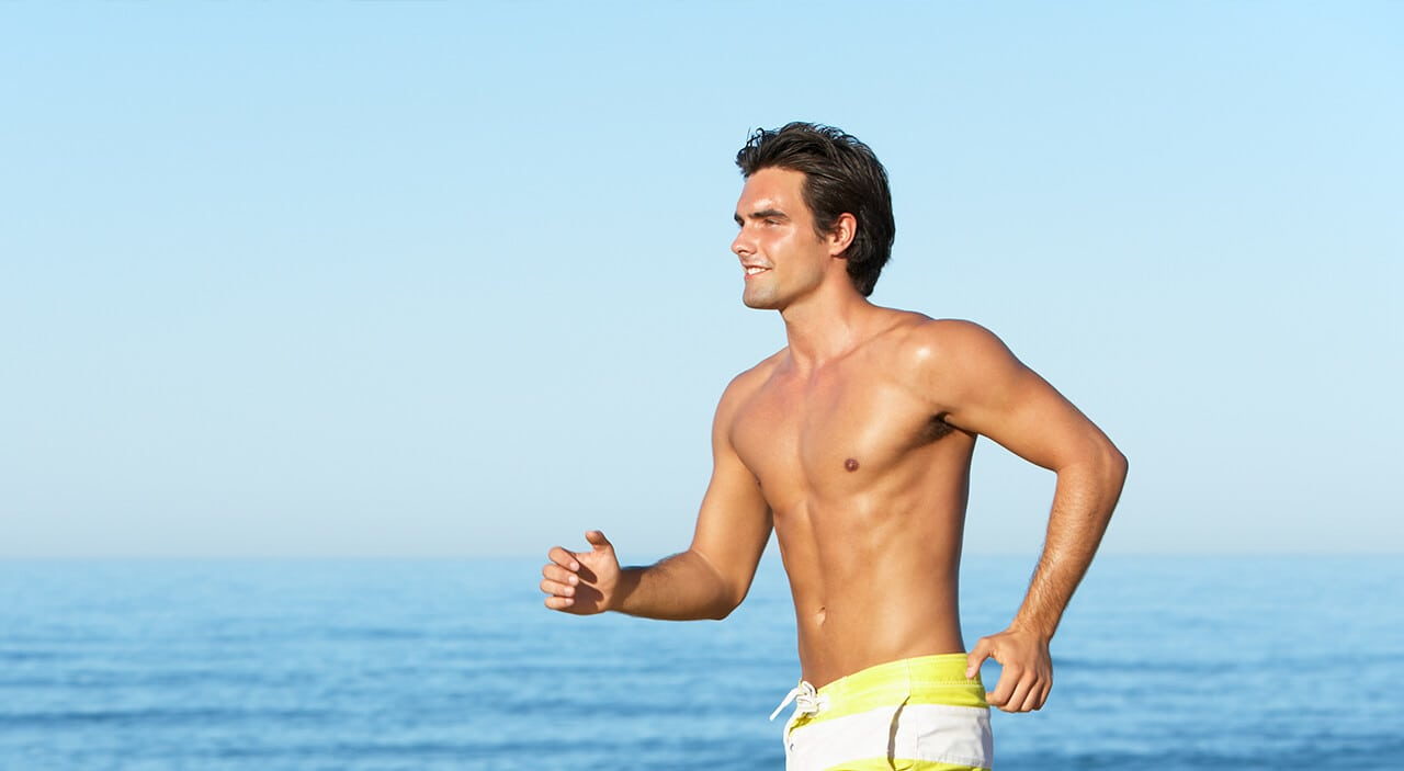 Man in swimming trunks running on beach in the sun.