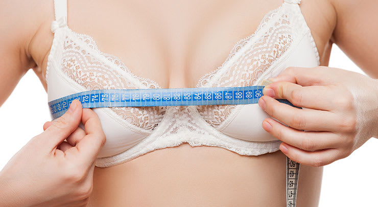 Woman holding a tape measure to her breasts to measure cleavage.