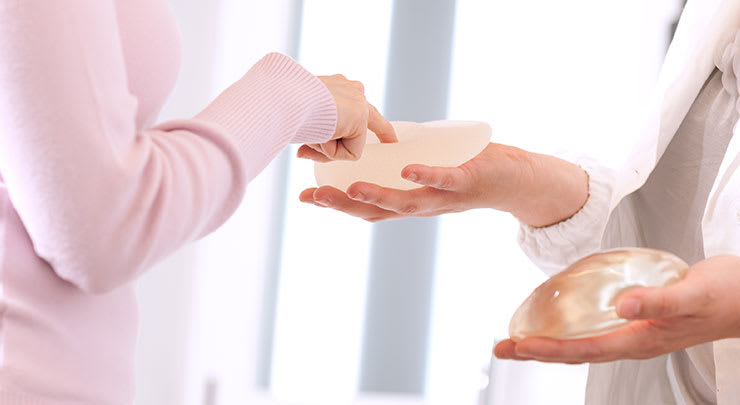 Doctor holding breast implants for female patient.